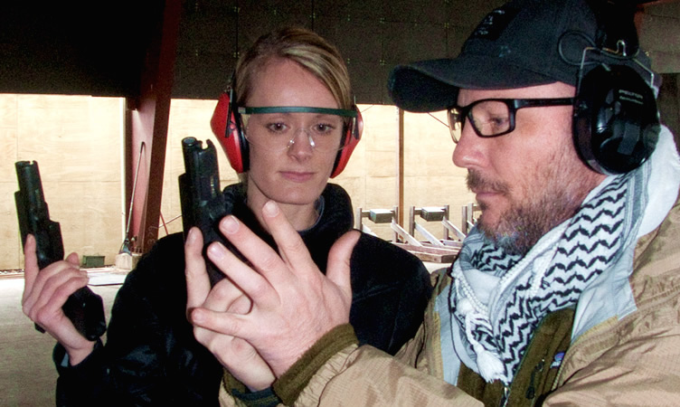 An Instructor shows a student how to handle a weapon.